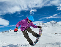 Snowboarder in mountains. Taking for the edge snowboard against the blue sky and clouds Stock Photos