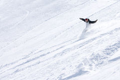 Snowboarder on mountainside. Male snowboarder sliding down slope of snowy mountainside Stock Photography