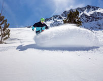 Snowboarder moving down. Freerider snowboarder moving down in snow powder Royalty Free Stock Photos