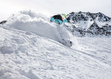 Snowboarder moving down. Freerider snowboarder moving down in snow powder Stock Image