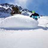 Snowboarder moving down. Freerider snowboarder moving down in snow powder Stock Photography