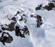 Snowboarder moving down in mountains Stock Photos