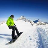 Snowboarder na pista nas montanhas altas Fotos de Stock