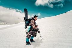 Snowboarder neemt op de weg toe bij de bovenkant van de berg stock foto