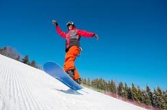 Snowboarder nell'aria mentre guidando sul pendio nelle montagne un bello giorno di inverno soleggiato fotografia stock libera da diritti