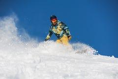 Snowboarder no sportswear brilhante que monta abaixo de uma inclinação de montanha do pó imagens de stock royalty free