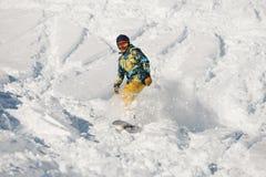 Snowboarder novo no sportswear brilhante que monta abaixo de uma inclinação de montanha do pó foto de stock royalty free