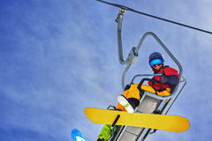 Snowboarder obsiadanie na chairlift i ono uśmiecha się, zakończenie Fotografia Stock
