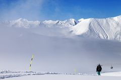 Snowboarder on off-piste slope and mountains in mist Stock Photography