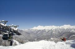 Snowboarder op de bovenkant van achtergrond van de berg de blauwe hemel stock afbeeldingen
