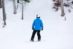 Snowboarder op helling bij toevlucht stock afbeeldingen