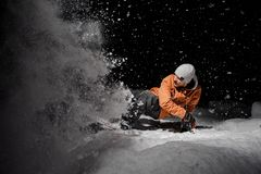 Snowboarder in orange jacket riding on a snowy hill at night. Snowboarder in orange jacket riding on a snowy powder hill at dark night on black background royalty free stock images