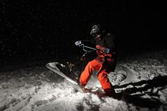Snowboarder in orange sportswear jumping on a snowy hill at nigh. Active and young snowboarder dressed in orange sportswear jumping on a snowy hill at night stock photos