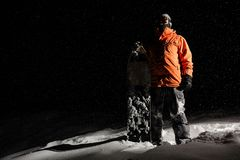 Snowboarder in orange sportswear and mask standing with a board. On a snowy hill at night stock photography