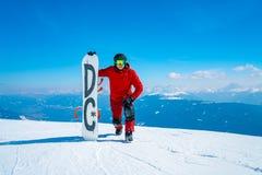 Snowboarder Oung стоя на верхней части горы стоковое фото rf
