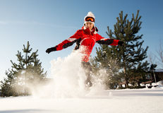 Snowboarder over blue sky in forest Stock Image