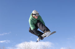 Snowboarder Performing Stunt Against Blue Sky. Low angle view of male snowboarder performing stunt against blue sky Royalty Free Stock Photography