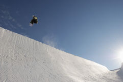 Snowboarder Performing Stunts In Park Against Blue Sky. On a sunny day Stock Photos