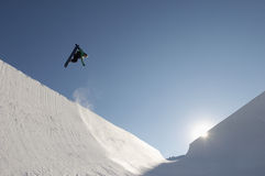 Snowboarder Performing Stunts On A Sunny Day At Park. Low angle view of snowboarder performing stunts in park against blue sky on a sunny day Stock Photo