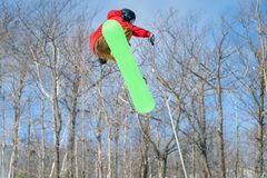 A snowboarder performs a mid-air trick in a terrain park royalty free stock photography