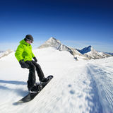 Snowboarder on piste in high mountains Stock Photos