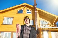 Snowboarder Posing against Wooden Chalet royalty free stock photo