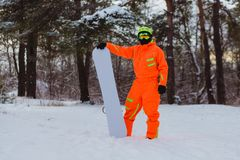 Snowboarder posing in winter forest. Snowboarder dressed in orange suit posing in winter forest royalty free stock photos