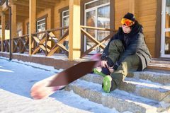 Snowboarder Putting On Boots. Full length portrait of modern young snowboarder putting on boots sitting on steps of wooden chalet at ski resort, copy space Royalty Free Stock Image