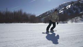 Snowboarder que aprecia um passeio da montanha em uma estância de esqui em um dia ensolarado vídeos de arquivo