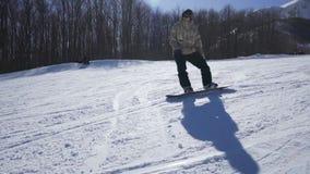 Snowboarder que aprecia um passeio da montanha em uma estância de esqui em um dia ensolarado filme