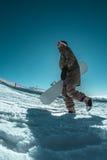 Snowboarder que camina contra el cielo azul fotografía de archivo libre de regalías