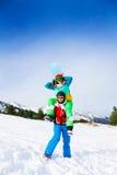 Snowboarder que detiene a la muchacha en sus hombros Fotografía de archivo libre de regalías