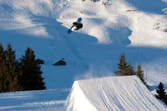 Snowboarder que executa um salto do estilo livre Fotografia de Stock Royalty Free