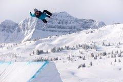 Snowboarder que gira fazendo uma garra no ar imagens de stock royalty free