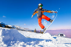 Snowboarder que lleva a cabo al tablero durante salto Imagen de archivo libre de regalías