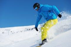 Snowboarder que monta abajo fotografía de archivo