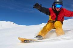 Snowboarder que monta rapidamente na inclinação seca do freeride da neve fotografia de stock royalty free