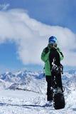 Snowboarder que se coloca con la snowboard en las montañas Imágenes de archivo libres de regalías