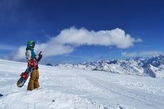 Snowboarder que se coloca con la snowboard en las montañas Fotografía de archivo