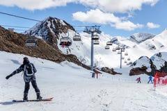 Snowboarder que se coloca en cuesta de montaña nevosa en la estación de esquí de Sochi Krasnaya Polyana en un día soleado Fotos de archivo