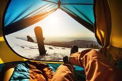 Snowboarder que se relaja en tienda en el fondo de la puesta del sol Imagenes de archivo