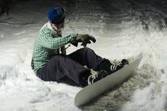 Snowboarder que se sienta en nieve imagenes de archivo