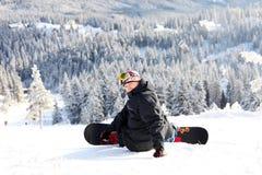 Snowboarder que se sienta en una cuesta de montaña Imágenes de archivo libres de regalías