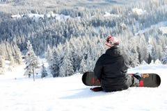 Snowboarder que senta-se em uma inclinação de montanha Imagens de Stock Royalty Free