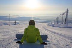 Snowboarder que senta-se na neve Imagem de Stock