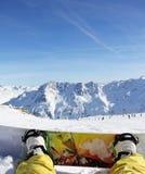Snowboarder que senta-se na neve Foto de Stock