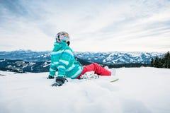 Snowboarder que senta-se na neve foto de stock royalty free