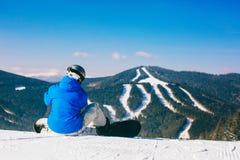Snowboarder que senta-se na neve contra montanhas Imagens de Stock Royalty Free
