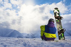 Snowboarder que senta-se na neve e que admira a paisagem do inverno Foto de Stock Royalty Free