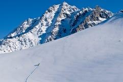 Snowboarder que sube al pico Imagen de archivo libre de regalías